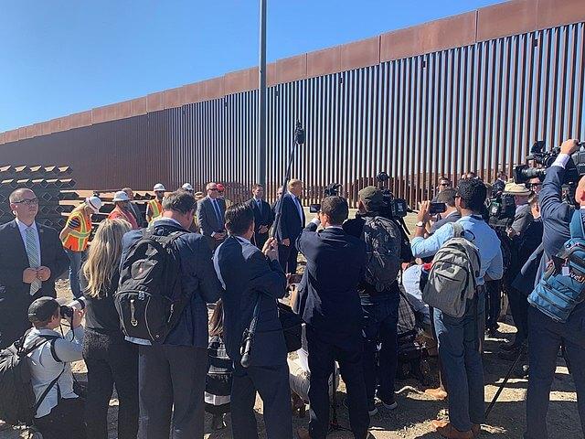 La nota es sobre la política de Trump y Biden en materia de derechos de los migrantes. La foto es de Trump en la frontera de México y Estados Unidos.