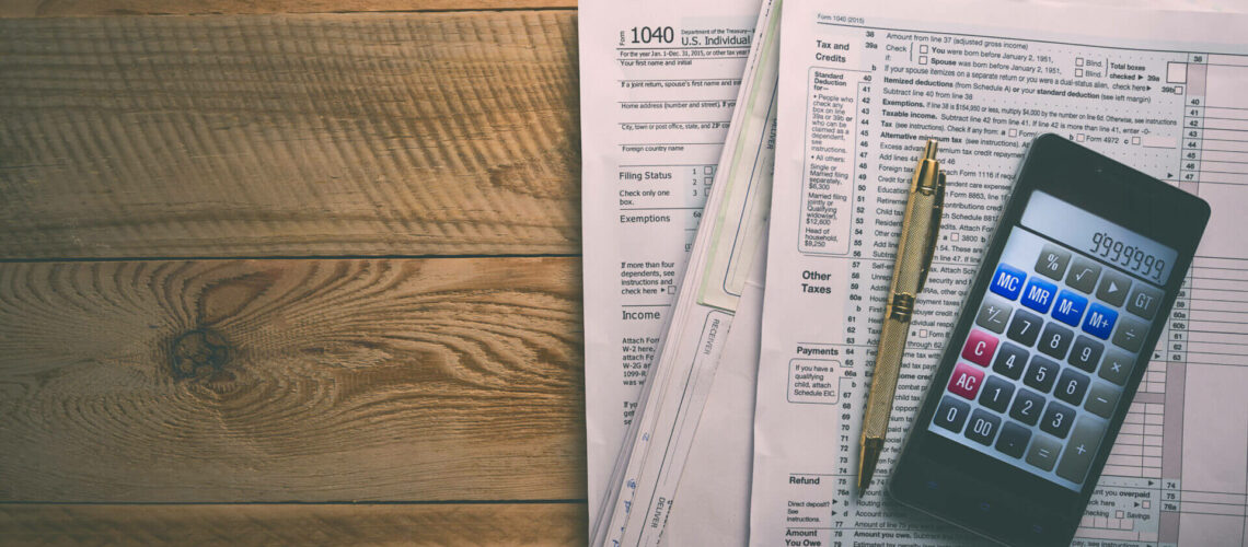 Filling 1040 tax form with smartphone calculator and pen
