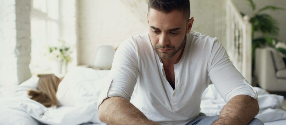 Upset young man sitting in bed suffer of problems while his girlfriend sleep in bedroom at home