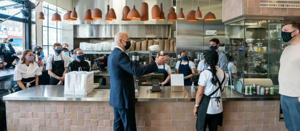 Nota sobre la reforma migratoria 2021 y su vínculo con la falta de mano de obra en los Estados Unidos. La imagen es del presidente Biden junto a trabajadores de una cafetería.