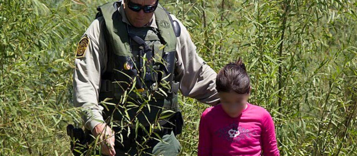 Nota informando sobre las novedades respecto al programa Permanecer en México. La foto es de un agente de la Patrulla Fronteriza junto a una niña migrante.