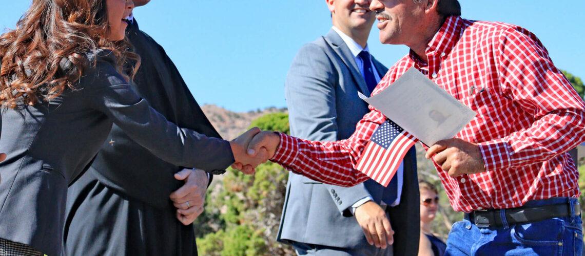 Nota explicando los requisitos para la ciudadanía americana 2021. La foto es de una ceremonia de naturalización realizada recientemente.