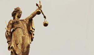 La nota es sobre la orden del Departamento de Seguridad Nacional para limitar los arrestos en zonas cercanas a los juzgados. La foto muestra la representación de la justicia.